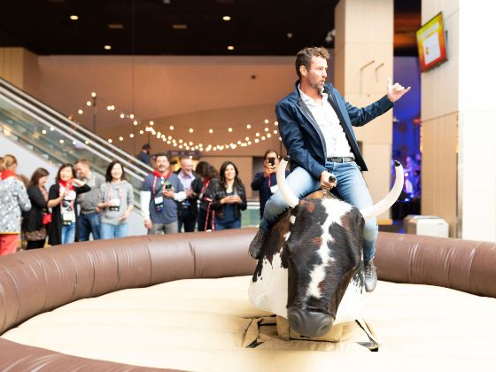 Man bull riding at a corporate event in the United Club Lounge spotlight 560x420